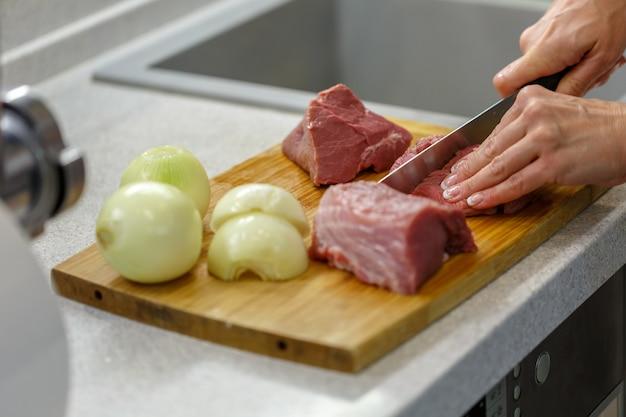 Mulher corta carne crua em pedaços grandes em uma placa de madeira