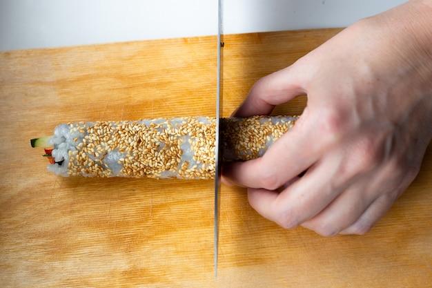 Mulher corta com uma faca uma folha de nori enrolada em um rolo em pequenos pedaços