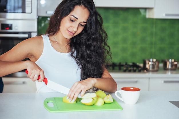 Mulher corta legumes juntos na cozinha.