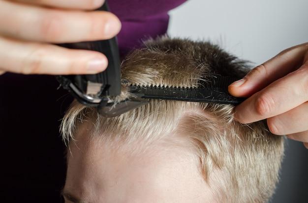 Mulher corta o cabelo do menino em casa. corte de cabelo em casa.