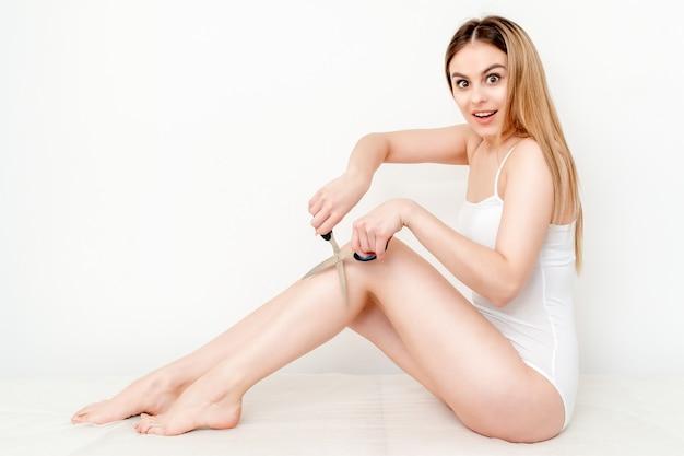 Mulher corta o cabelo nas pernas com uma tesoura