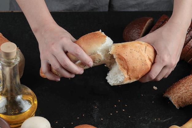 Mulher corta o pão ao meio na mesa escura com ovos e um copo de óleo.
