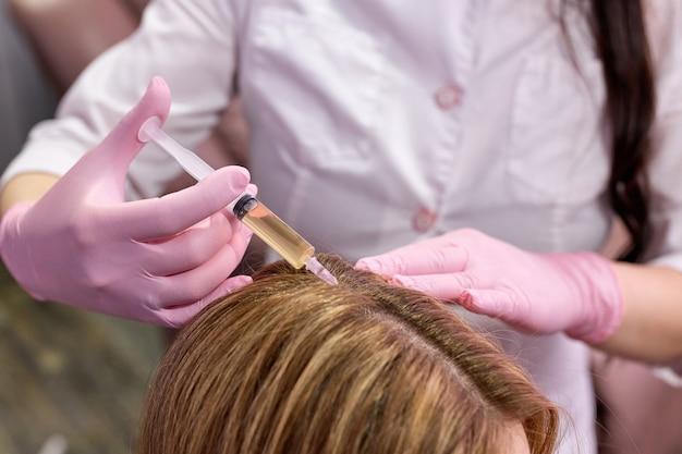 Mulher cortada no consultório do tricologista recebe injeções na pele da cabeça com as mãos de um médico profissional segurando uma seringa descartável