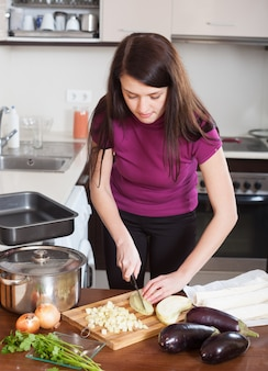 Mulher cortando a berinjela para torta de peixe