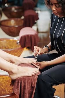 Mulher cortando as unhas dos pés com um cortador de unhas