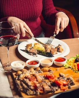 Mulher cortando bife de frango grelhado servido com pimentos grelhados, salada e vinho