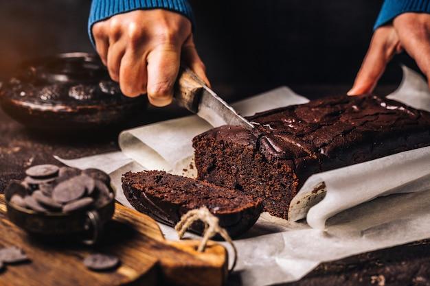 Mulher cortando bolo de pão de chocolate escuro