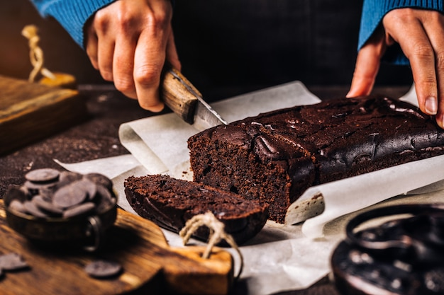 Mulher cortando bolo fresco com chocolate