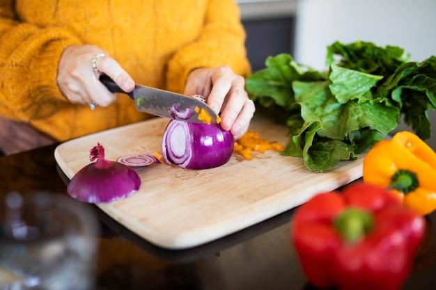 Mulher cortando cebola roxa e cozinhando na cozinha