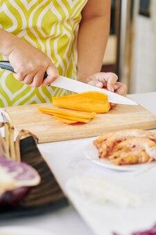 Mulher cortando cenoura