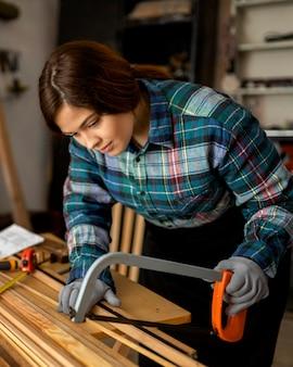 Mulher cortando com serra