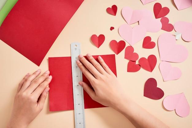 Mulher cortando corações de feltro vermelho, artesanato caseiro
