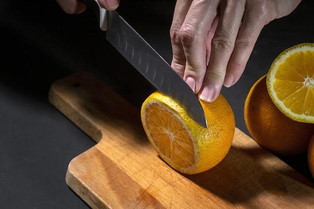 Mulher cortando fatias de laranja frescas e saudáveis em uma placa de madeira
