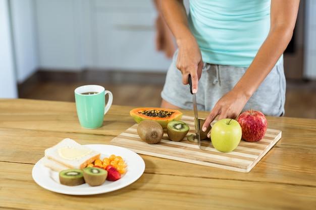 Mulher cortando frutas no balcão da cozinha