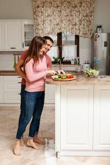Mulher cortando legumes abraçados pelo marido