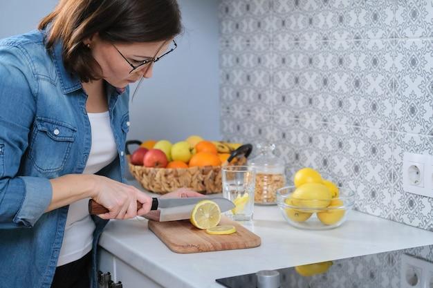 Mulher cortando limão com faca em uma tábua na cozinha