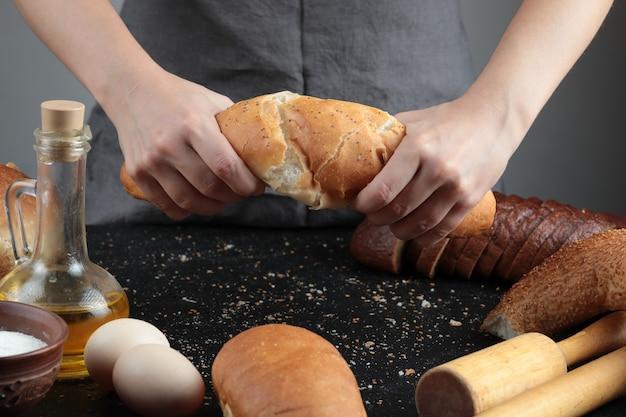 Mulher cortando o pão ao meio na mesa escura com ovos, tigela de farinha e copo de óleo.