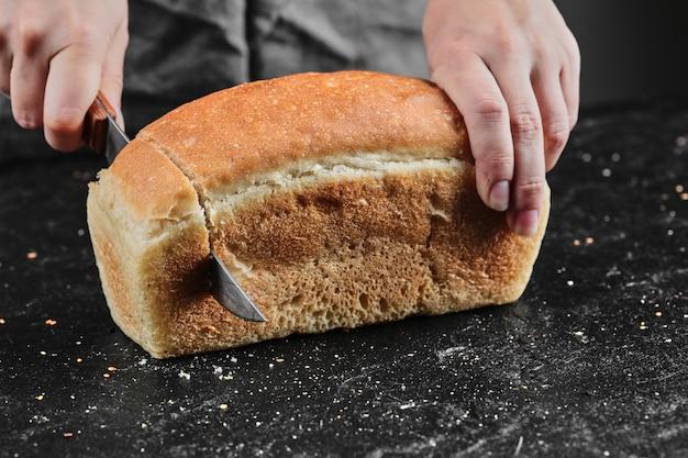Mulher cortando pão com faca na mesa escura.