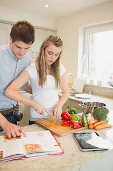 Mulher cortando pimentas com homem lendo livro de receitas