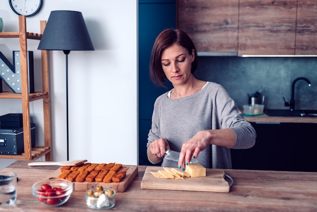 Mulher cortando queijo gouda na tábua de madeira