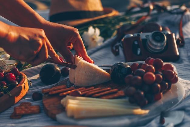 Mulher cortando queijo na tábua de madeira com queijo e frutas e câmera, chapéu e flores na praia.