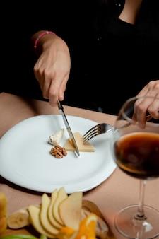 Mulher cortando queijo parmesão do prato de queijo