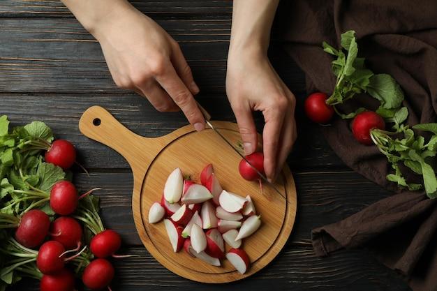 Mulher cortando rabanetes em uma tábua de madeira