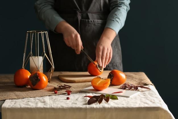Mulher cortando saborosa fruta de caqui na mesa