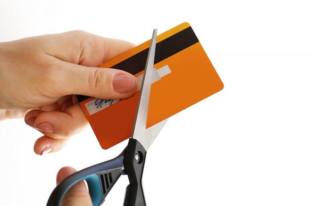 Mulher cortando seu cartão de crédito com uma tesoura