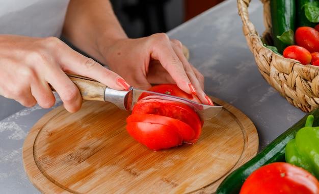 Mulher cortando tomate em uma placa de corte vista de alto ângulo sobre uma superfície cinza