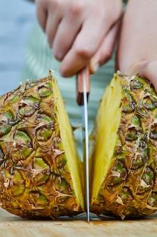 Mulher cortando um abacaxi fresco em uma tábua de madeira, close-up