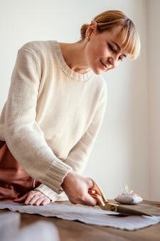 Mulher cortando um tecido em vista lateral