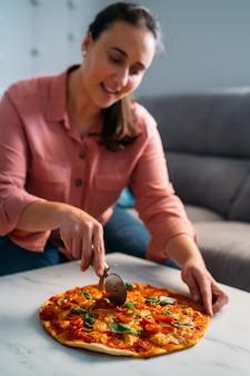 Mulher cortando uma pizza tradicional italiana margarita em sua sala de estar