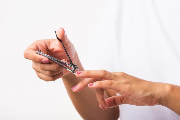 Mulher cortando unhas no dedo usando um cortador de unhas