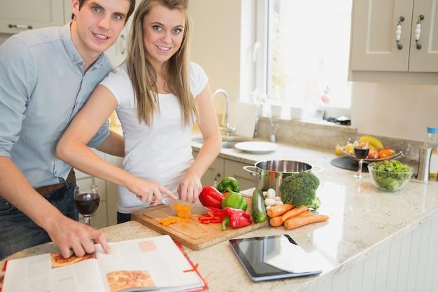 Mulher cortando vegetais com homem lendo o livro de culinária Foto Premium