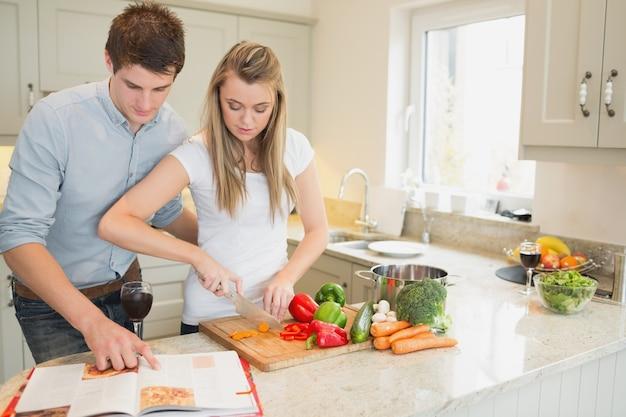 Mulher cortando vegetais com homem lendo o livro de receitas Foto Premium