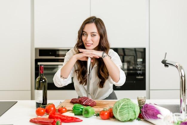 Mulher cortar carne com uma faca na cozinha e cozinhar