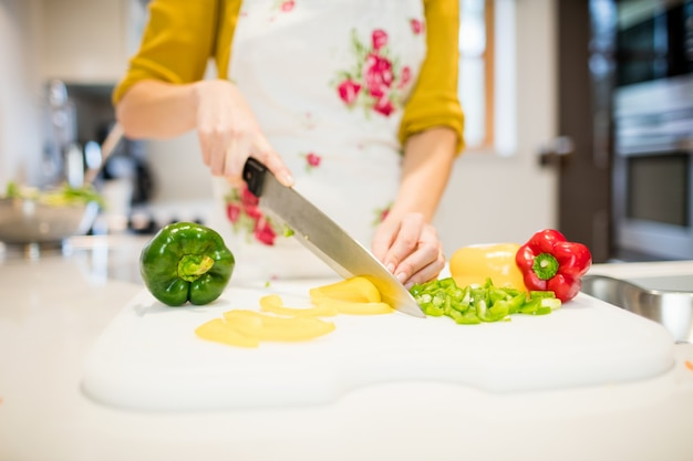 Mulher cortar legumes na tábua de cortar