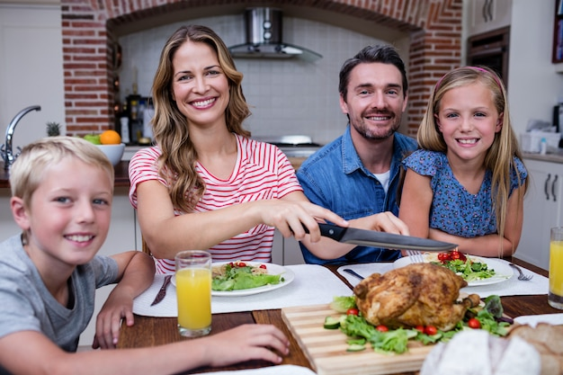 Mulher, corte, peru assado, enquanto, tendo, refeição, com, seu, família