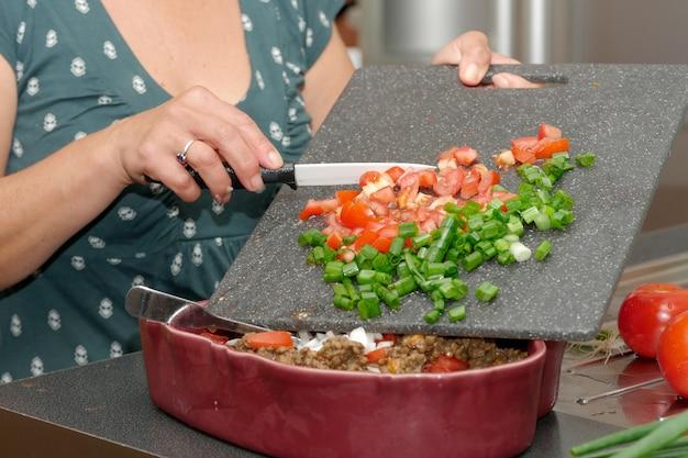 Mulher, corte, tomate, com, a, faca, ligado, prato