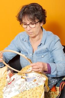Mulher costura para terminar uma colcha.