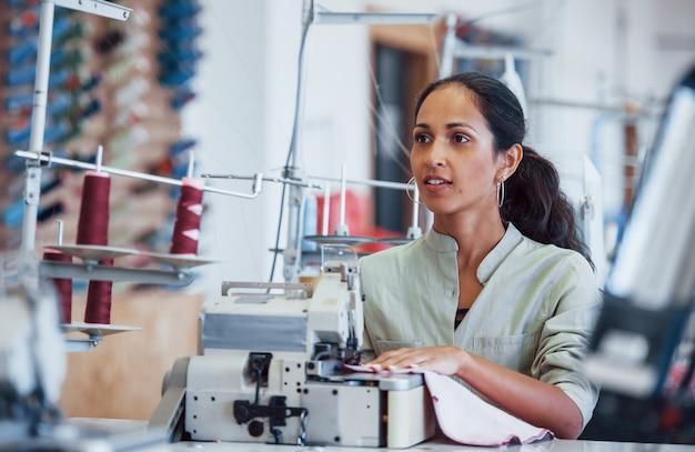 Mulher costureira costura roupas na máquina de costura da fábrica.