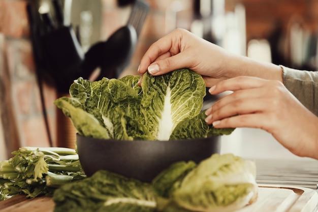 Mulher cozinhando com alface
