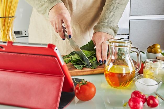 Mulher cozinhando de acordo com o tutorial da master class virtual online, e olhando a receita digital, usando tablet touchscreen enquanto cozinha uma refeição saudável