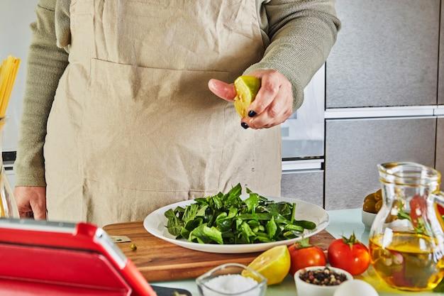 Mulher cozinhando de acordo com o tutorial de master class virtual online, e olhando a receita digital, usando tablet touchscreen