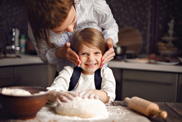 Mulher cozinhando e se divertindo com menina