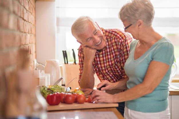 Mulher cozinhando e seu marido alegre