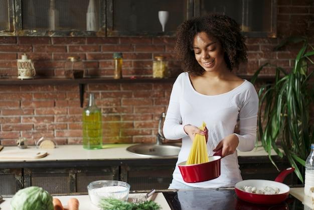 Mulher cozinhando espaguete