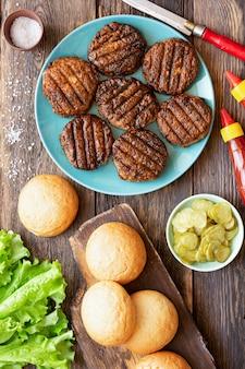 Mulher cozinhando hambúrguer de carne em casa na cozinha