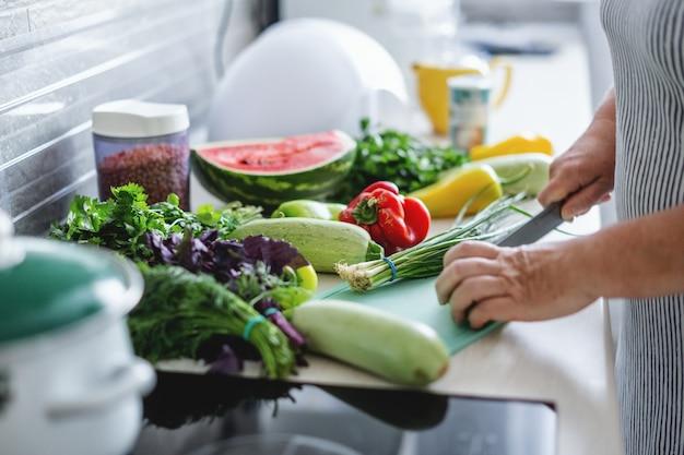 Mulher cozinhando legumes na cozinha.